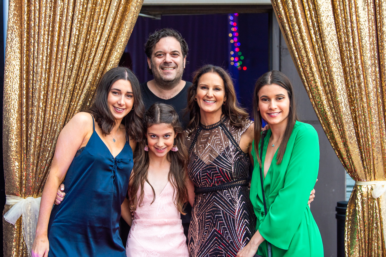 Jenna's Bat Mitzvah family photo in front of gold sequin entrance draping hire melbourne