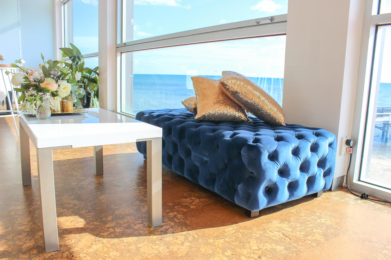 Side View of Blue Velvet Ottoman Hire Melbounre with Gold Pillows