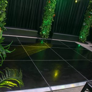 black dance floor with vine covered truss