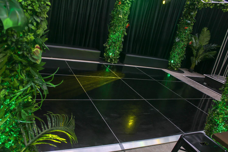 black dance floor with vine covered truss