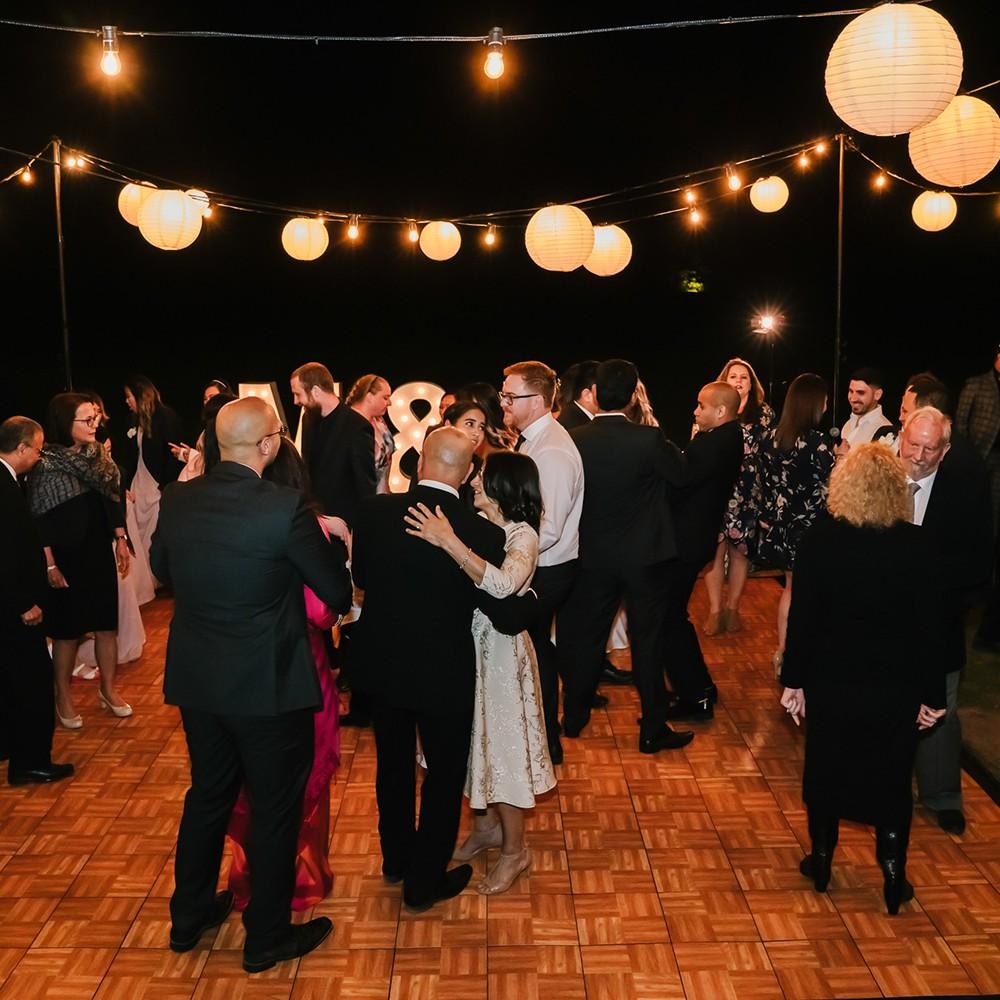 dancing on an outdoor wedding dance floor with overhead festoon lanterns in melbourne