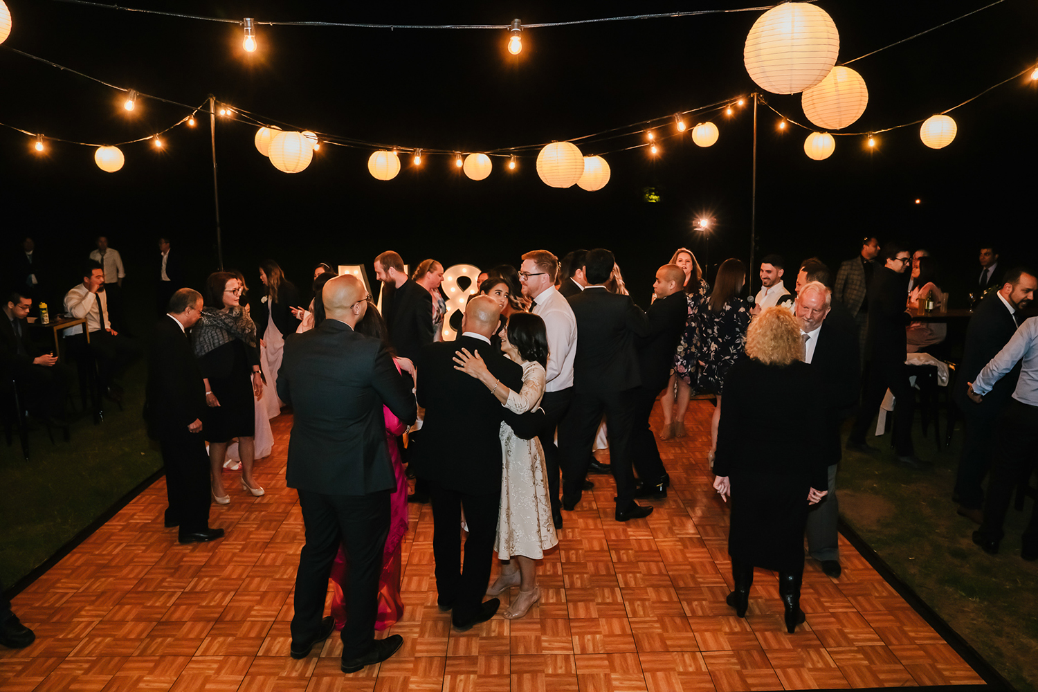 dancing on an outdoor wedding dance floor with overhead festoon lanterns in melbourne